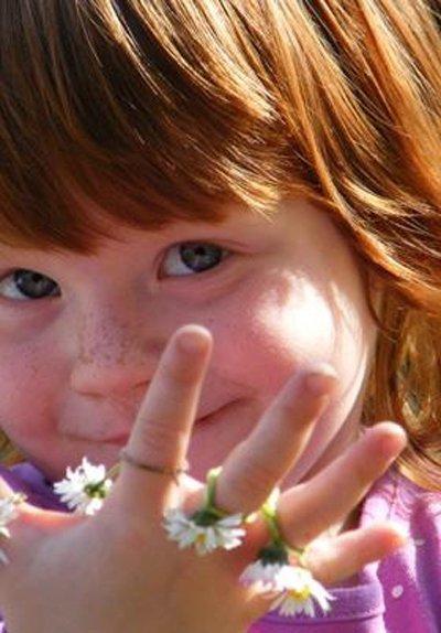 bambina coi capelli rossi e gli occhi azzurri e con fiori tra le dita