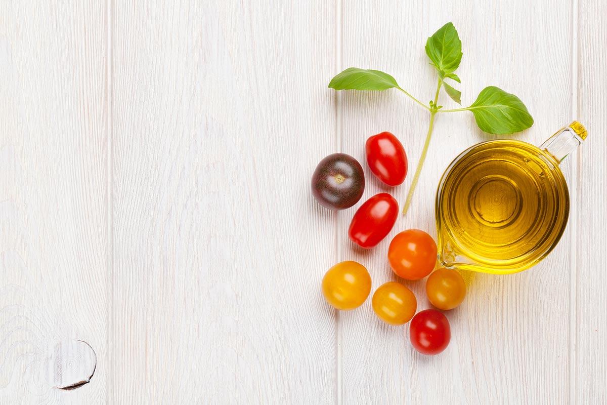 Ingredienti essenziali per un'ottima pizza: olio di oliva, pomodori e basilico