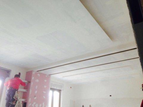 muratore lavora un controsoffitto all' interno di un appartamento