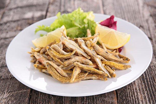 delle alici fritte, insalata e fette di limone