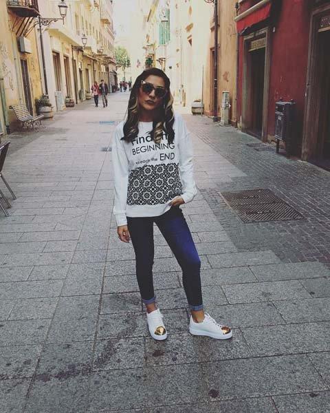 modella in posa con jeans e maglia