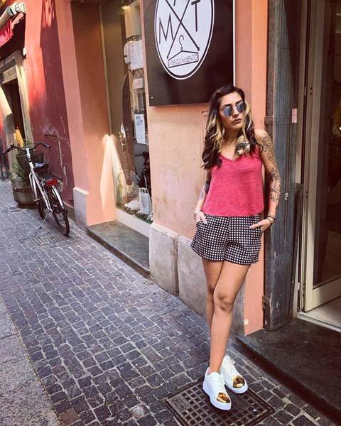 modella appoggiata al negozio con pantaloncini e maglia rosa