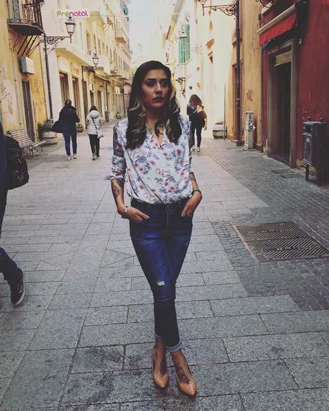donna in posa per un a foto con jeans e maglietta a fiori in mezzo al centro citta