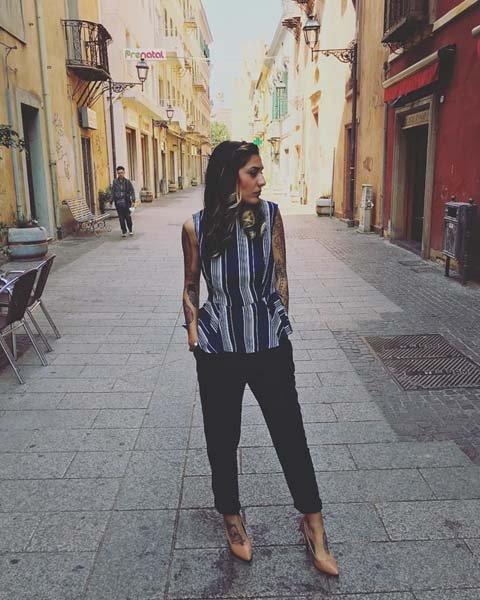 modella che guarda di lato con pantaloni neri e canottiera a righe