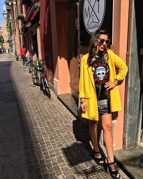 modella con giubotto giallo e maglia sportiva nera con uno scheletro disegnato