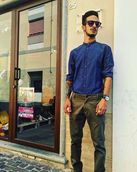uomo con pantaloni marroni e maglia blu