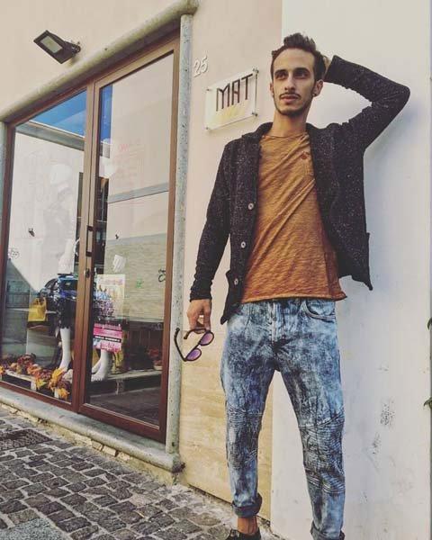 modello con pantaloni in jeans maglia arancione e giubotto di jeans