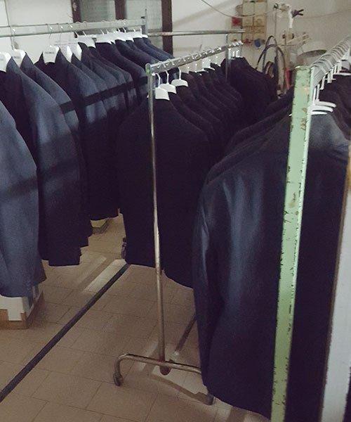 Un altro angolo dell'impresa dove si vedono uniformi di uomo pronti in attesa di essere consegnati