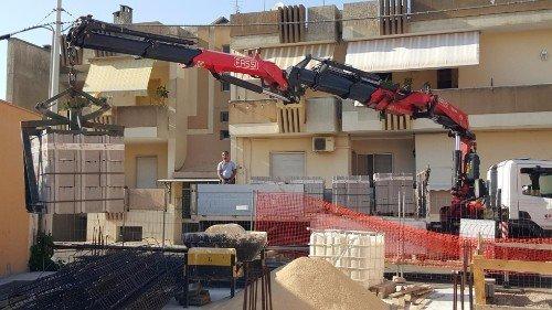 Autogru scaricando un pale con mattoni di cemento