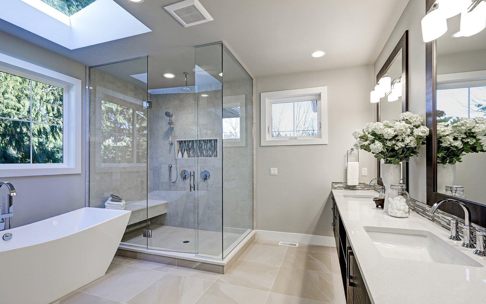 un bagno moderno con vista di due lavabi, un vaso con dei fiori, una vasca e un ampio box doccia