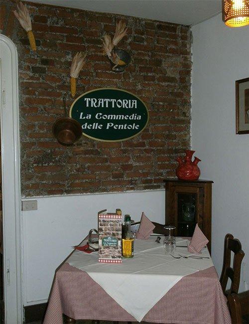 Angolo del ristorante con una tavola preparata e il nome del ristorante in una parete di mattoni