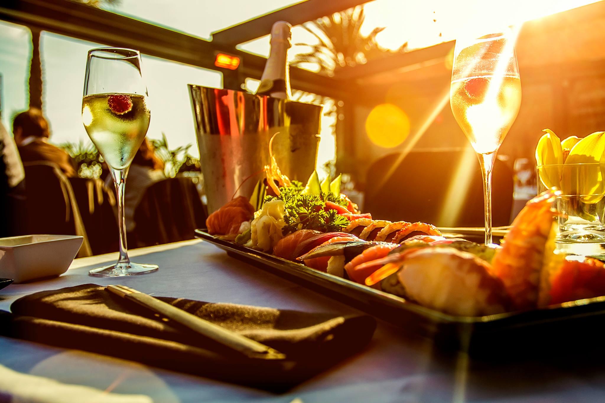 un vassoio con del sushi e dei bicchieri di vino bianco