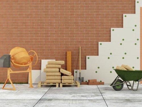 Betoniera, sacchi di cemento e carriola con sfondo di muri in mattone