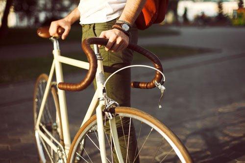un uomo che sorregge dal manubrio e dal sellino  una bici da corsa di color bianco