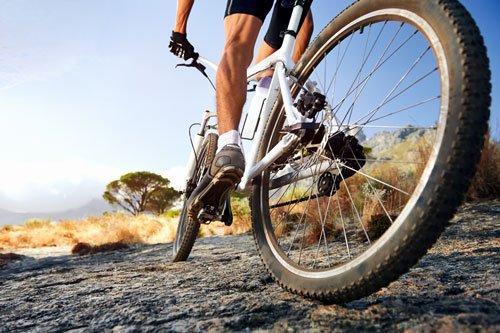 vista delle ruote e delle gambe di un ciclista che pedala su una strada rocciosa