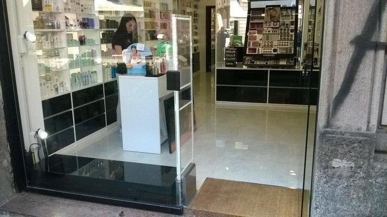 Una barriera antitaccheggio e una commessa in un negozio di cosmetici