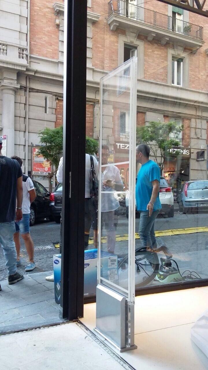 Una barriera antitaccheggio in un negozio e delle persone fuori sul marciapiede