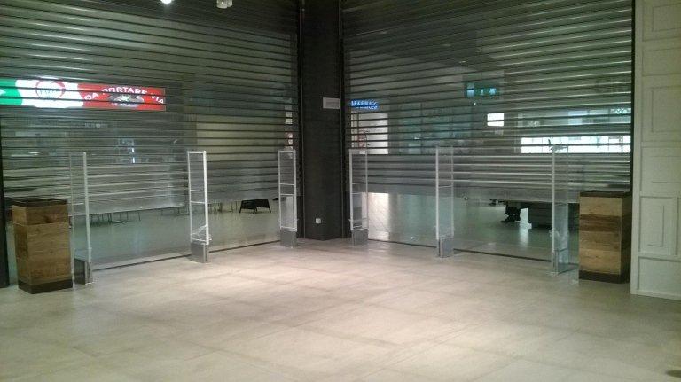 Delle barriere antitaccheggio all'esterno di un negozio con le serrande abbassate