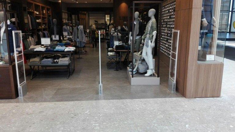 Tre barriere antitaccheggio e vista di un negozio di vestiti