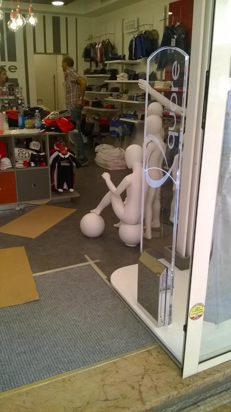Una barriera antitaccheggio con scritto quore e vista di un negozio di abbigliamento per bambini