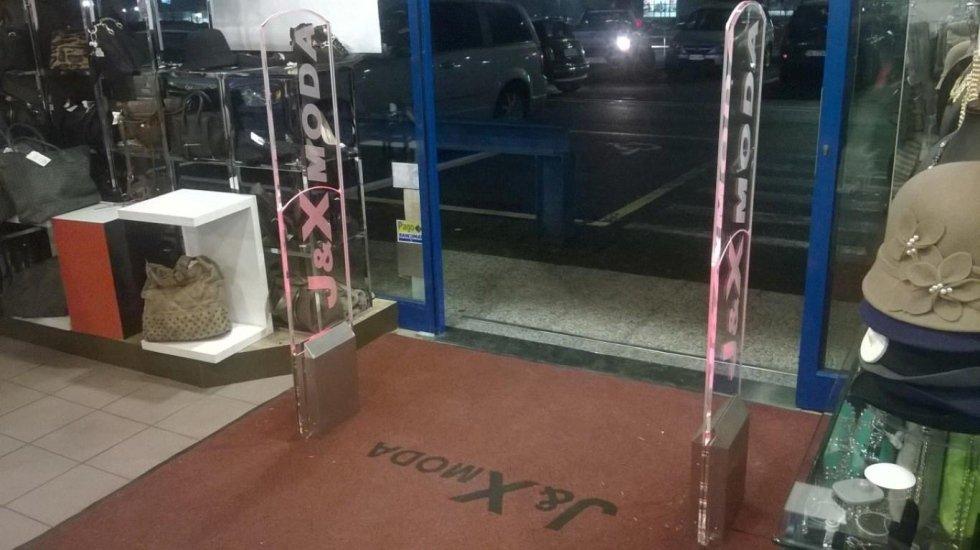 Due barriere antitaccheggio con scritto j&x moda all'interno del negozio