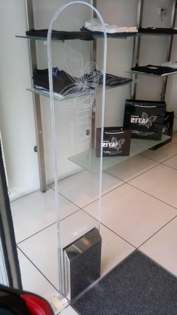 Una barriera antitaccheggio con il disegno di una farfalla e la scritta RITA all'interno di un negozio