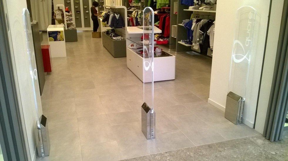 Tre barriere antitaccheggio con scritto quore e vista di un negozio di abbigliamento