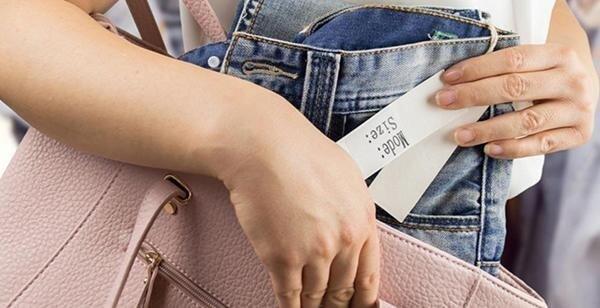 Due mani che tengono un paio di jeans e una di pelle borsa rosa