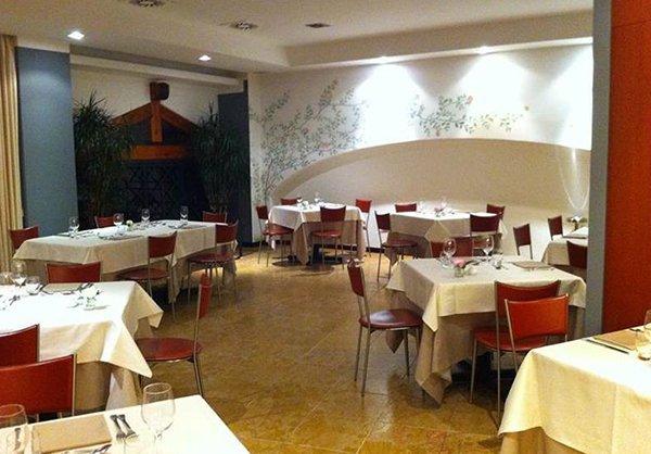 Vista generale del ristorante,semplice ma accogliente,un arco bianco in rilievo questa coperto di rami verdi