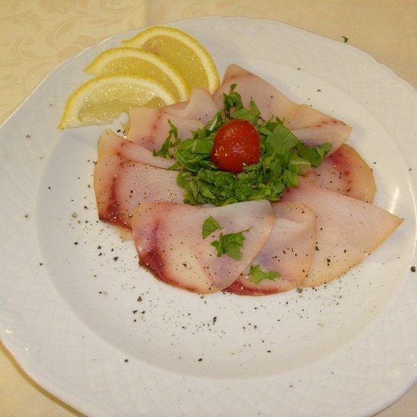 Carpaccio di pesce con base di pomodoro e tocchi di rucola con un po' di limon