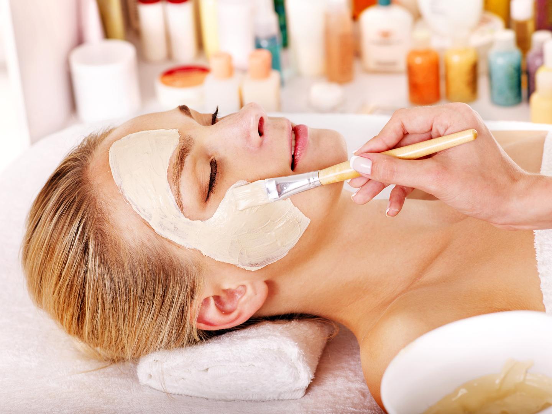 Una donna mentre un estetista le spalma una crema bianca sul viso con un pennello