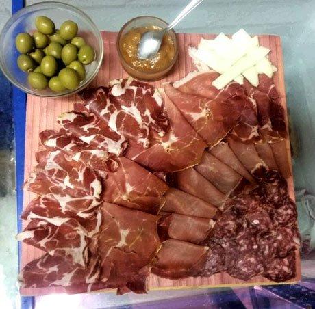 Tavola di affettati, formaggi e olive per iniziare