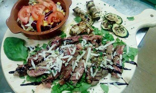 Un tagliere di roastbeef al sangue, zucchine grigliate e insalata