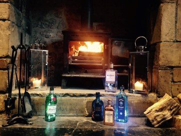 spirits bottles in front of a fireplace