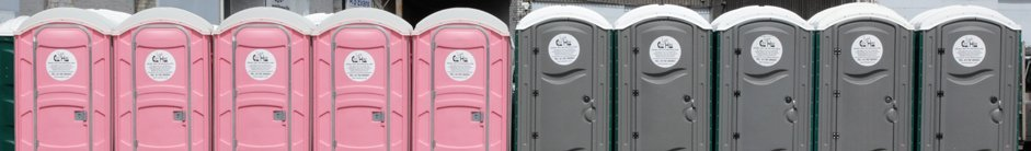 A row of pink and grey portable toilet units at depot in Swansea