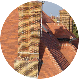 Clay tiles on a house with a tall red brick chimney
