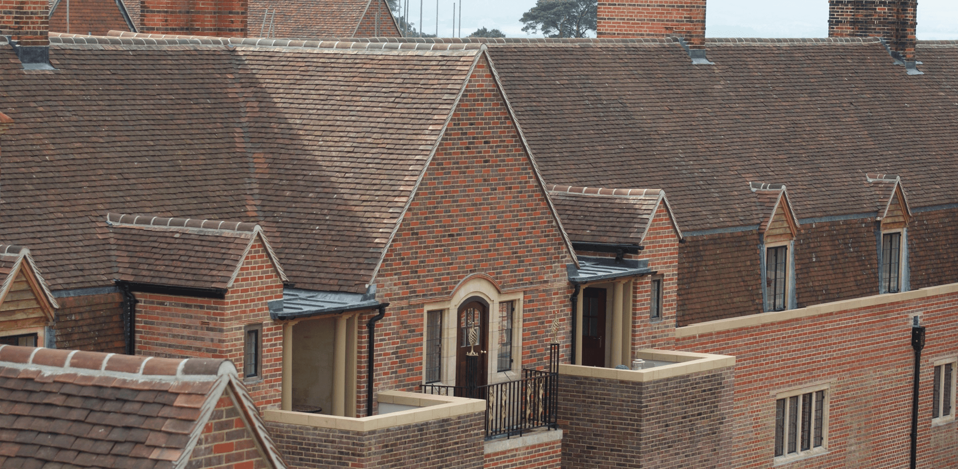 A close up of a large red tiled roof with matching red bricks