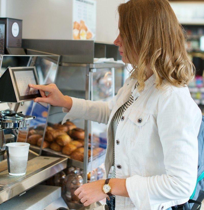donna a un distributore automatico di caffè