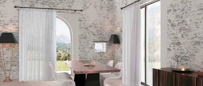 vista interna di una casa con tavolo in legno e tenda bianca