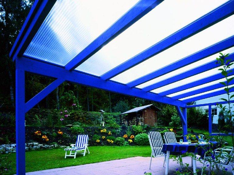 Una tettoia in plexiglass sorretta da una struttura di ferro blu in un giardino