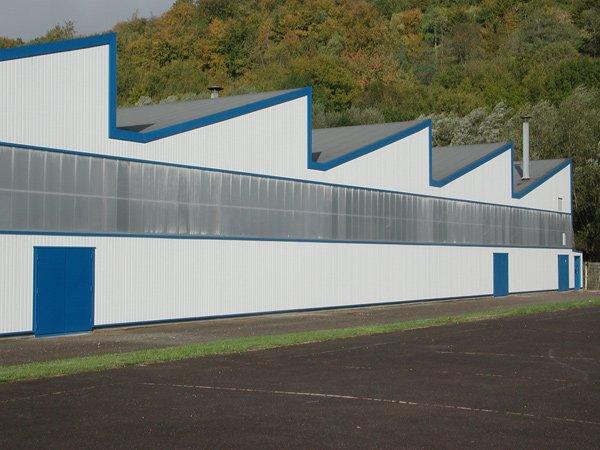 Uno stabile industriale bianco e blu con del plexiglas sulla facciata