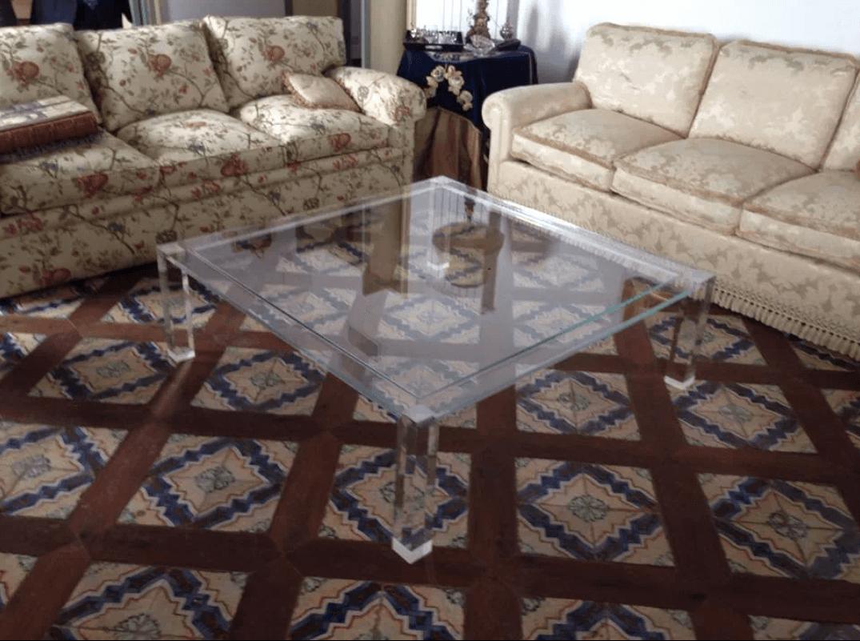 Un tavolino in plexiglass trasparente e sopra un rivista