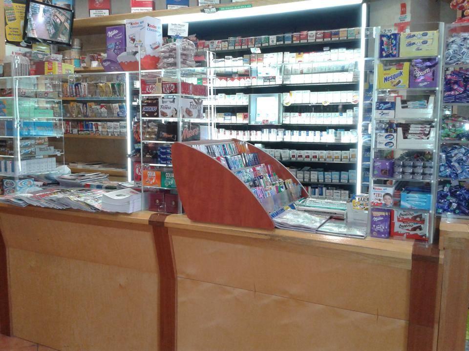 Un bancone di un negozio con dietro degli scaffali in plexiglas