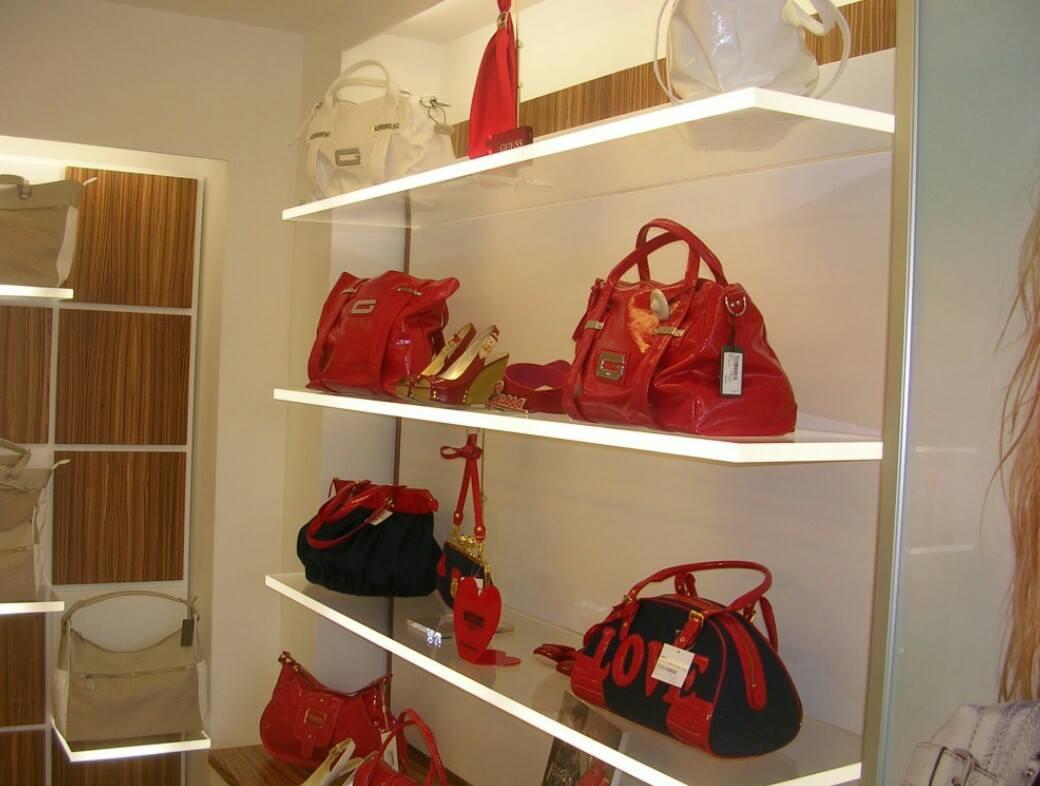 Delle mensole trasparenti con delle borse in un negozio