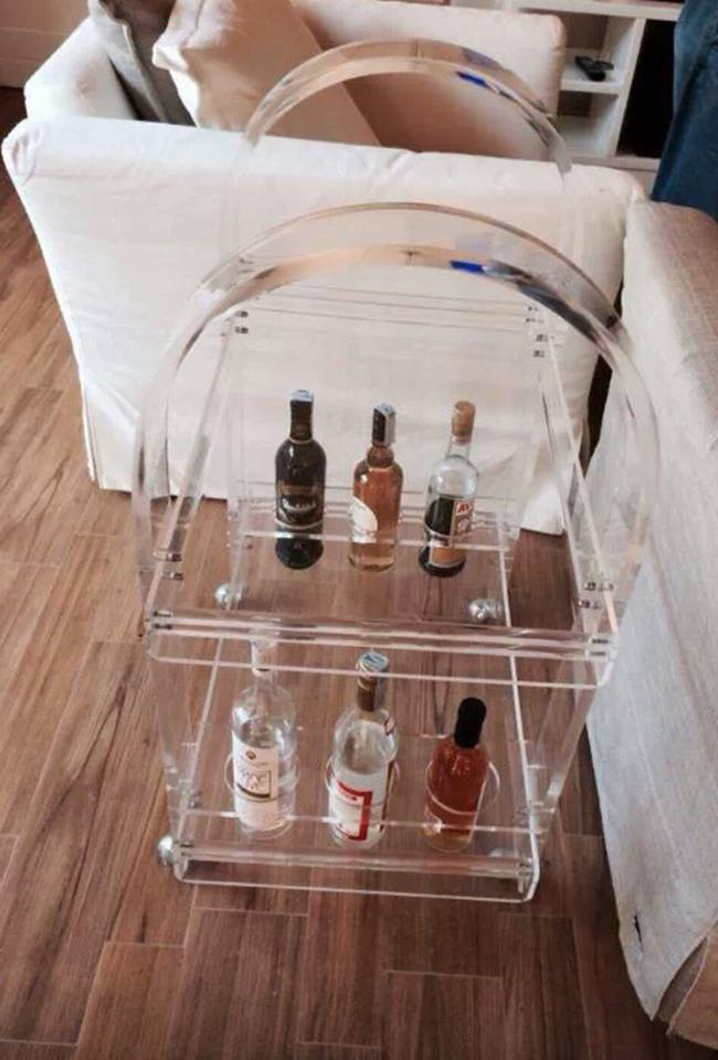 Un carrello in plastica trasparente con delle bottiglie di liquore