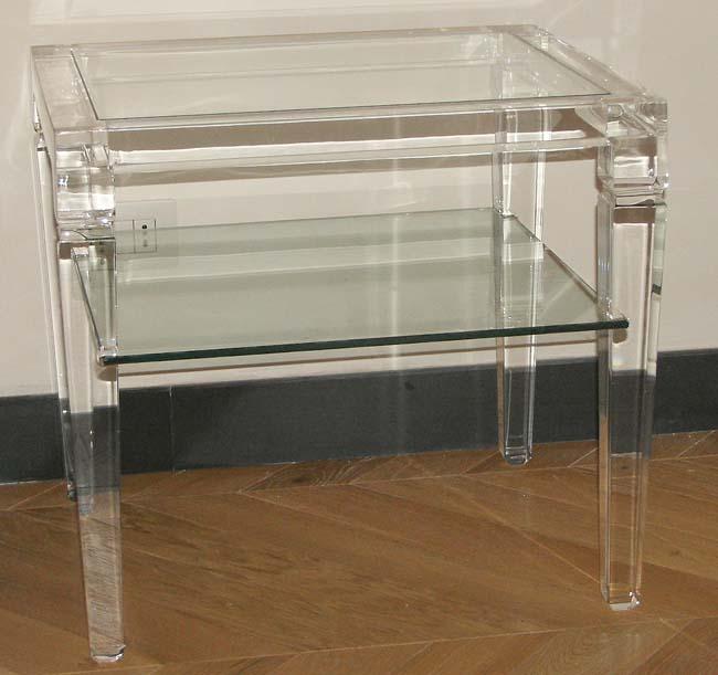 Un tavolino con due mensole in plastica trasparente