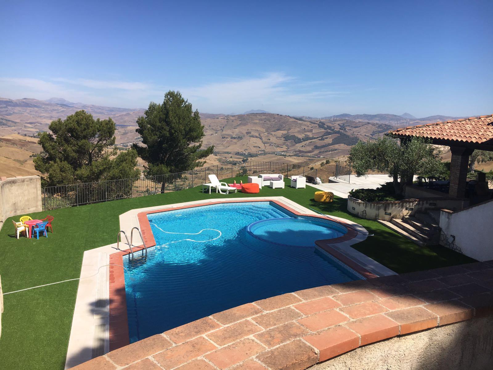 Una piscina in una villa e vista delle colline