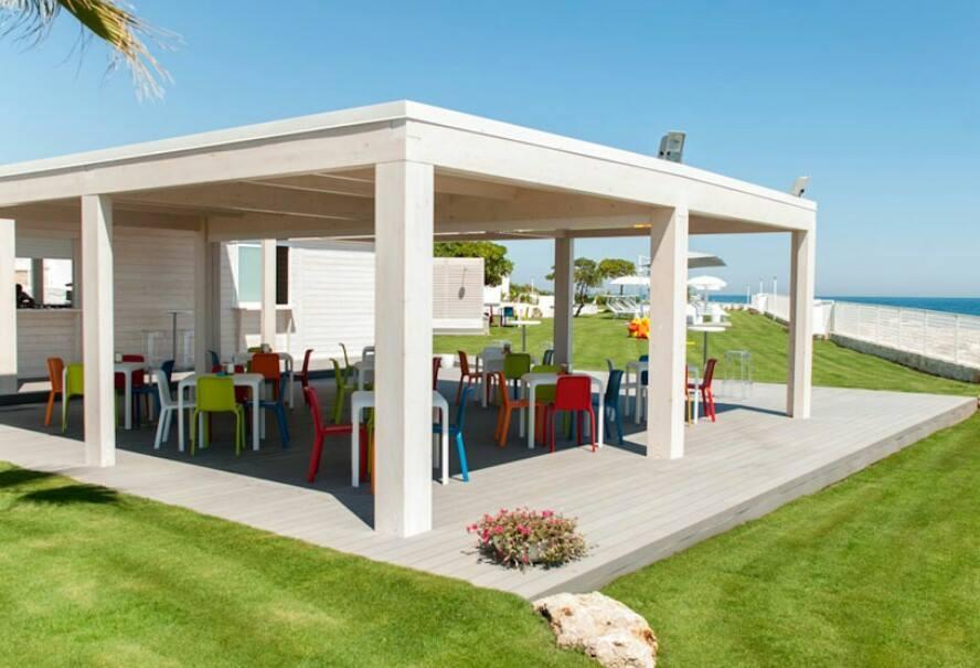 Dei tavoli e delle sedie colorati sotto un tetto