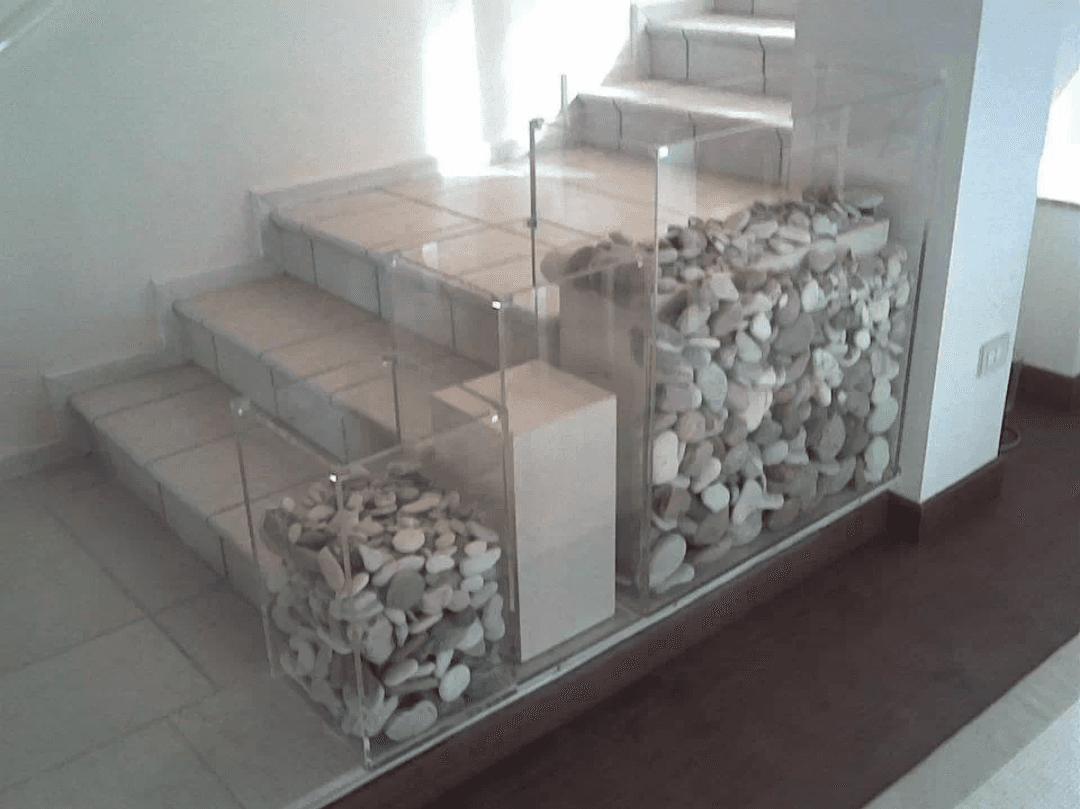 Delle scale e accanto degli scompartimenti in plastica con dentro dei sassi