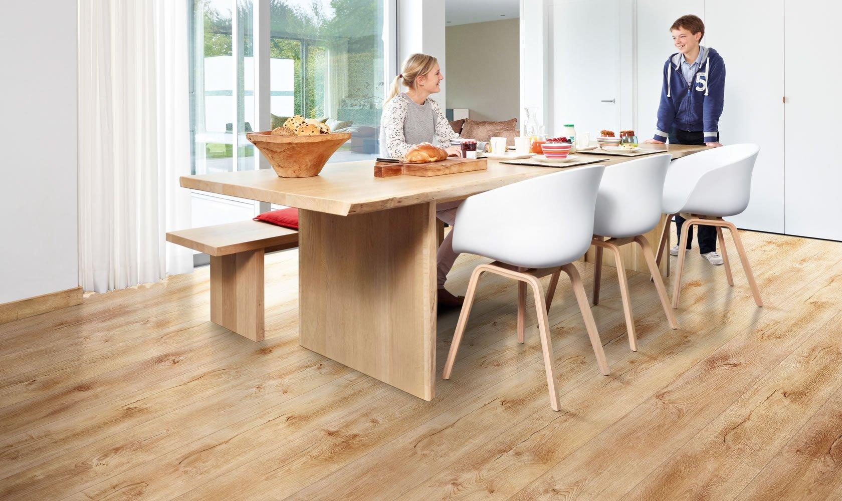Un tavolo in legno con una panchina e delle sedie di plastica di color bianco